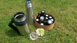 Thermos of elderflower tea and a box of samples of wild food